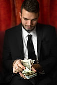 young man counting usa dollars