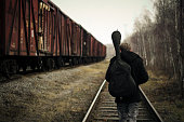 Young guitarist goes along the train on rails.