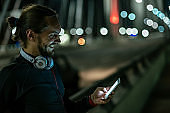 handsome man typing text message at night after working out