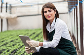Girl holding tablet device while crouching next to a field