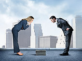 Businesswoman And Businessman Looking Down At Small Stack Of Money