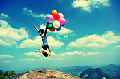 cheering woman jumping with colorful balloons on mountain peak