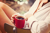 Morning coffee. Woman holds a red coffee cup