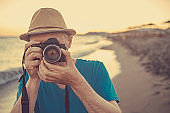 Man photographing through vintage camera outdoors