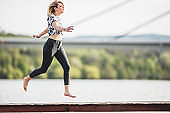 Carefree woman jumping on a pier near the river.