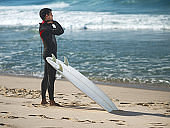 Young surfer preparing for surfing and looking at view.