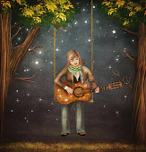 The boy sits on the swing in the forest  and plays  on   guitar