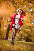 Young carefree woman having fun in autumn day.