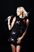 Beautiful Singing Girl. Beauty Woman with Microphone over black background.