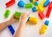 Baby girl playing with colorful blocks on white background