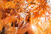 Carefree woman among branches in autumn day.