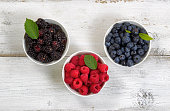 Bowls filled with freshly picked berries on rustic white wooden