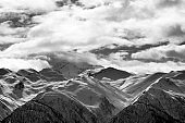 Black and white view on snowy mountains and cloudy sky