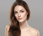 Young beautiful woman face portrait on gray background