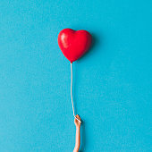 Doll hand with heart shaped baloon. Minimal concept. Flat lay.