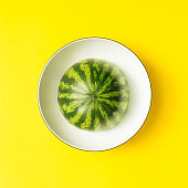 Watermellon in a bowl on yellow background.