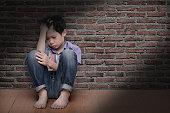 sad boy sitting on floor