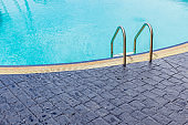 The view of metallic ladder entrance to blue swimming pool.
