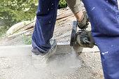 Construction worker cutting a reinforced concrete pillar