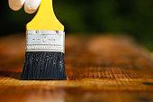 Paintbrush sliding over wooden surface, protecting wood