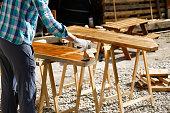 Worker applying fresh wood treatment paint