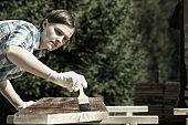 Woman applying fresh wood treatment paint