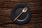 black empty plate fork spoon on wooden table background