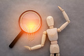 wooden man magnifying glass with light bulb paper cut shape