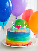 Rainbow cake and cupcakes. Balloons on the background