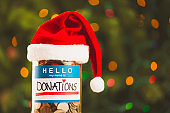 Donation money jar with Santa hat for Christmas charities