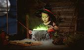 Halloween. child girl witch preparing  potion in cauldron