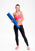 Beautiful happy fitness woman standing and holding yoga mat