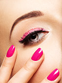 Closeup woman face with pink nails near eyes