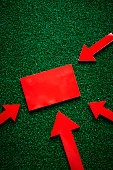 Arrows and red card on artificial grass