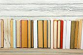 Books on grunge wooden table desk shelf in library. Back