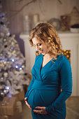 Young beautiful pregnant woman on christmas background