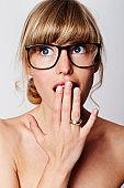 Blue eyed blond in eyeglasses, surprised