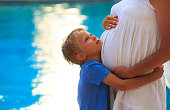 little boy hugging pregnant mother tummy at beach