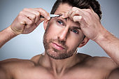 Man plucking eyebrows with tweezers