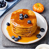 Pumpkin pancakes with maple syrup and blueberries Grey stone background