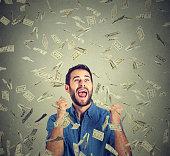 happy man celebrates success screaming under money rain