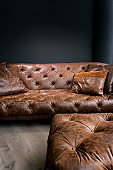 Vintage Brown Leather Sofa under Black Empty Wall