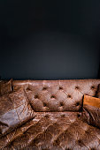 Detail of Vintage Brown Leather Sofa under Black Empty Wall