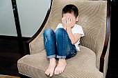Lonely child sitting on chair