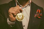 Elegant bearded man holding gold medal