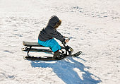 Small kid having fun while sledging on a snow.