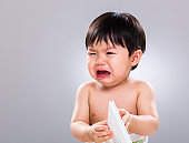 Crying Chinese toddler looking at piece of paper