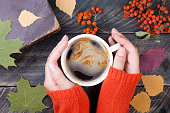 Female hands holding cup of coffee on autumn wooden background
