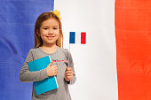 Girl with flag and book against French banner