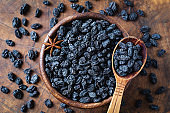 Black raisins in wooden bowl